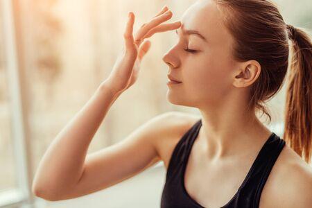 Photo pour Young woman massaging third eye chakra - image libre de droit