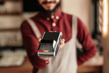 Photo for Modern hipster waiter handing over payment terminal in cafe - Royalty Free Image