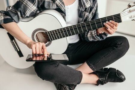 Photo pour Crop woman with smartphone learning to play guitar - image libre de droit