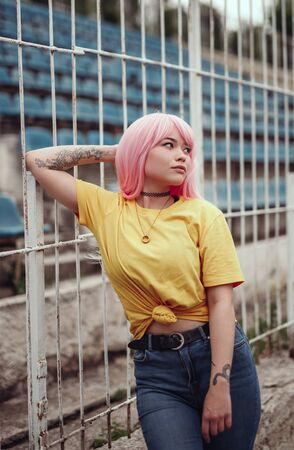 Photo pour Beautiful young Asian woman with pink hair on stadium - image libre de droit