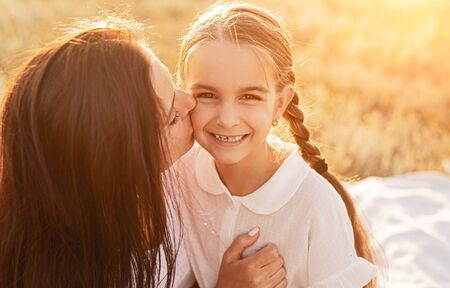 Photo pour Mother hugging and kissing daughter with love on picnic in field - image libre de droit