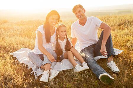 Photo pour Cheerful family resting in field - image libre de droit