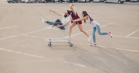 Foto de Women pushing shopping cart with male friend - Imagen libre de derechos