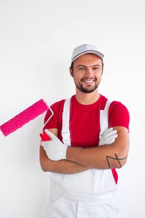 Photo pour Professional male painter with roller smiling at camera - image libre de droit