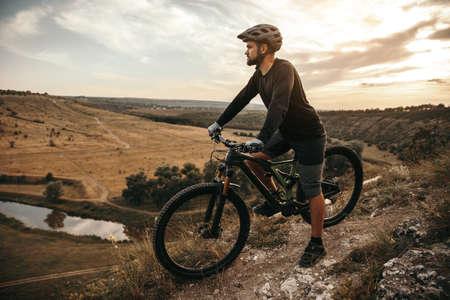 Photo pour Confident cyclist admiring highlands in countryside - image libre de droit