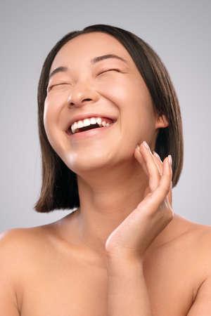 Photo pour Excited ethnic female touching clean skin - image libre de droit