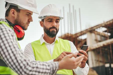 Photo pour Architects working with smartphone on construction site - image libre de droit
