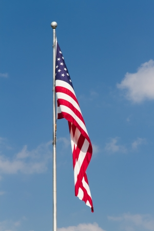 The flag of the United States of America flies from a flagpole in this vertical orented photograph with great detail and vibrant colors