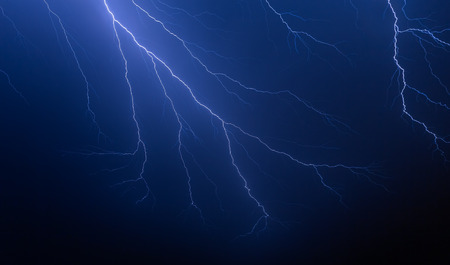 Bolts of lightning branch and fork in the night sky during a summer thunderstorm.