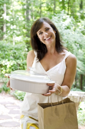 Pretty woman bringing a covered dish to a neighbor