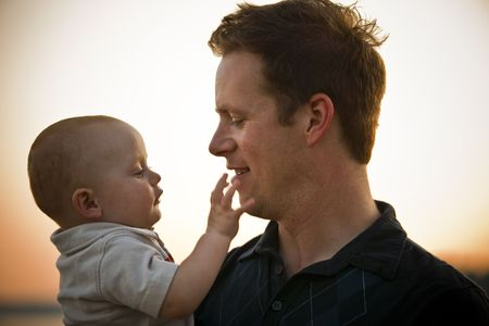 Photo for Father and baby at sunset, with baby touching father's chin. Horizontal. - Royalty Free Image
