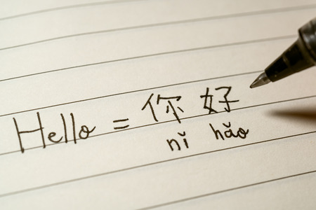 Photo pour Beginner Chinese language learner writing Hello word Nihao in Chinese characters and pinyin on a notebook macro shot - image libre de droit