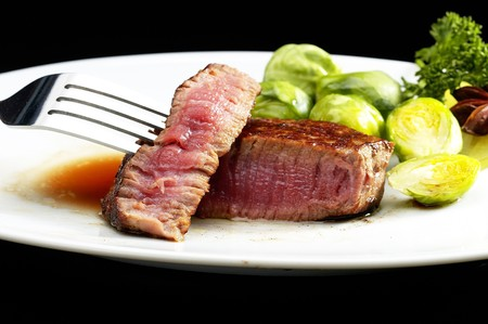 juicy filet mignon on plate with brussel sprout over black background