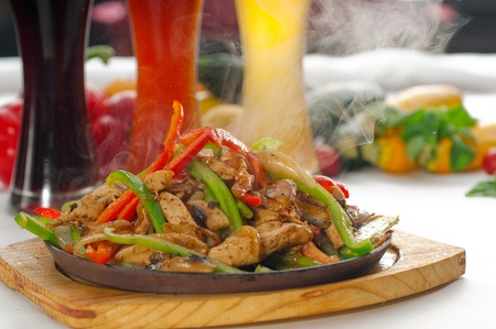 original fajita sizzling smoking hot served on iron plate ,with selection of beer and fresh vegetables on background ,MORE DELICIOUS FOOD ON PORTFOLIO