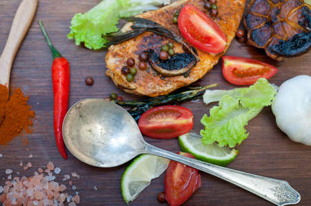 Photo for wood fired hoven cooked chicken breast on wood board with herbs spices and vegetables - Royalty Free Image