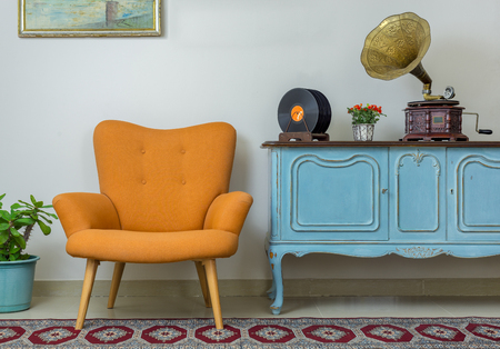Photo pour Vintage interior of retro orange armchair, vintage wooden light blue sideboard, old phonograph (gramophone), vinyl records on background of beige wall, tiled porcelain floor, and red carpet - image libre de droit