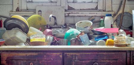 Photo pour Pile of dirty utensils in a kitchen washbasin - image libre de droit