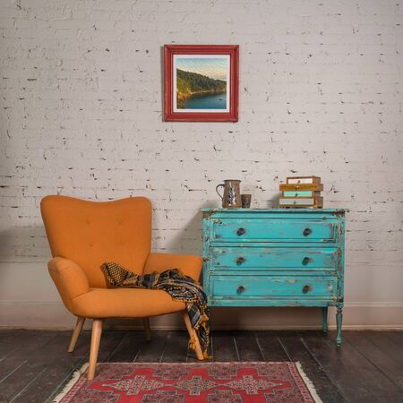 Photo pour Bright orange retro armchair with plaid against white brick wall with shabby chic vintage turquoise cabinet in living room and hanged painting, - image libre de droit