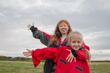 Mother and daughter outdoor and cloudy sky background
