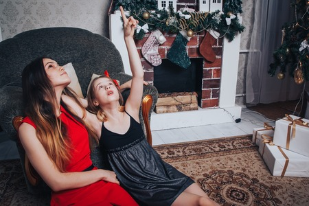 Photo pour Two girls sisters have relax and fun in a nice room decorated for Christmas and the New year - image libre de droit