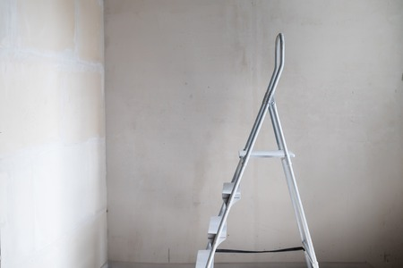 White aluminum step ladder in room with white walls