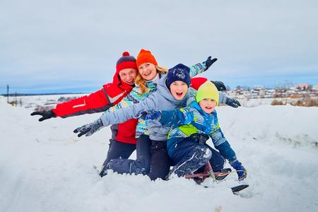 Photo pour Portrait of a family with four people having fun in the snow - image libre de droit