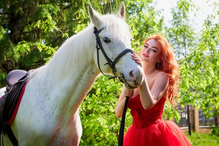 Photo for Portrait of a beautiful girl with red hair in a red dressy dress near with a white horse on a green nature in a Park or forest on a summer day. - Royalty Free Image