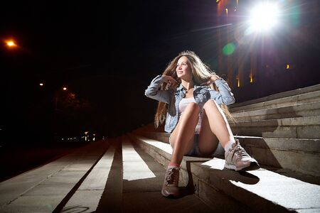 Photo for Young beautiful brunette woman with long hair on the steps of stairs on a city street at night and colored lights of flash near her - Royalty Free Image