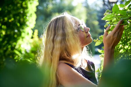 Foto de Pretty teenage girl 14-16 year old with curly long blonde hair in beautiful adult dress in the green park in a summer day outdoors. Beautiful outdoors portrait - Imagen libre de derechos