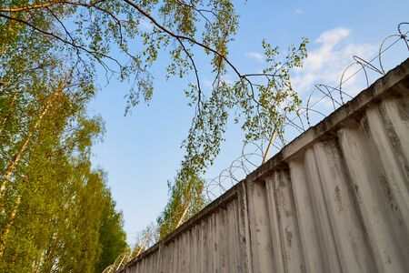 High concrete fence with barbed wire on summer day