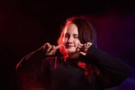 Photo pour Portrait of chubby teen girl illuminated by red light and black background. Model in a photo shoot with colored light - image libre de droit