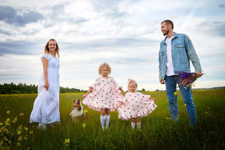 Photo pour Family including two young parents and daughters on a walk in a meadow with grass and flowers. Dad, mom, girls relaxing and having fun in nature on a summer day with clouds - image libre de droit