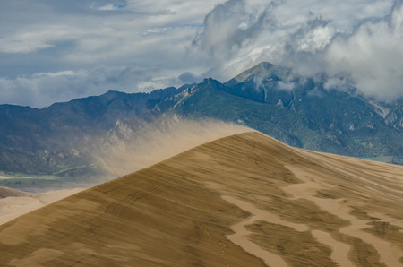 A windy day produces large amounts of saltation, sand blowing off the rims of the dunes