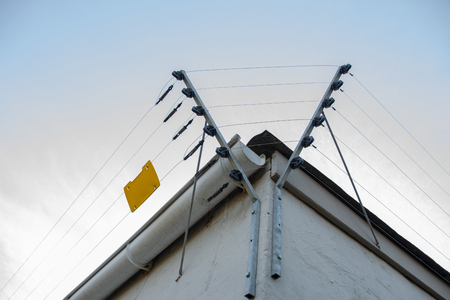 Photo pour A Close up view of electric fencing around the top side of a white building - image libre de droit