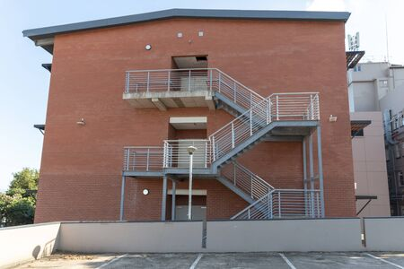 Photo for A close up view of a metal stair case going up the side of a newly built building  - Royalty Free Image