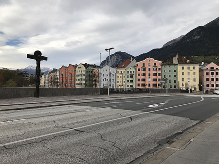 Innsbruck, Austria - October 31, 2018:  Sculpture and pastel buildings surrounding River Inn in Innsbruck, Austria.