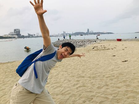 An asian man strolling on Pattaya beach, Thailand in the morning.