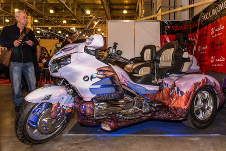 Winter 2015. Morning. Russia. Moscow. Crocus-Expo. Exhibition Motopark-2015 (BikePark-2015). The exhibition stand of the studio GL-Audio. Tricycle (Trike) Honda. Visitors are looking the stand.