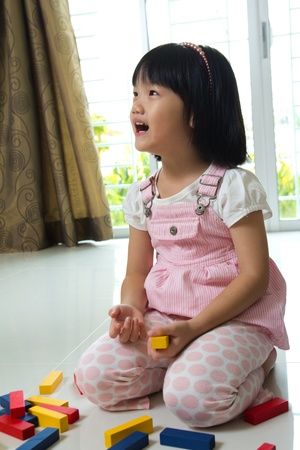 Little Asian girl is playing with blocks toy