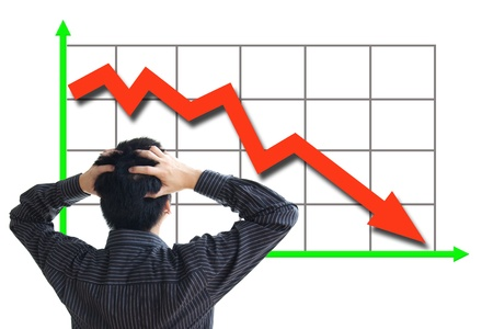 Frustrated business man looking at the falling graph of a stock market struck in financial crisis