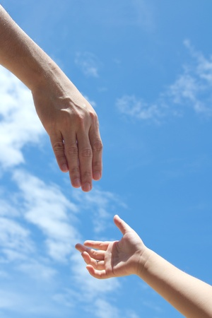 Photo for One adult hand reaches out to help child hand in need - Royalty Free Image