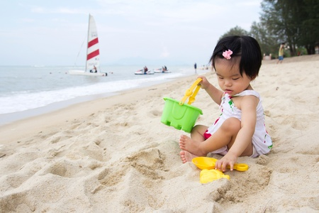 Photo for Happy little baby girl playing sand on beach with bucket and spade - Royalty Free Image