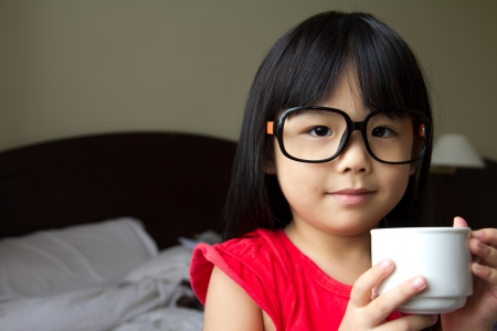 Portrait of a little girl wearing spectacles and hold a cup in hotel room