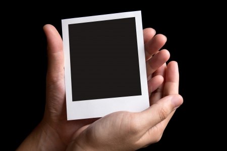 Blank instant photo frame in palm isolated in black background