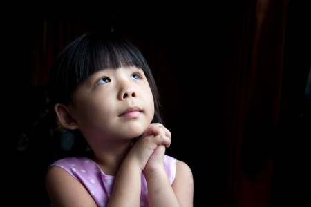 Little child is making a wish isolated in dark background