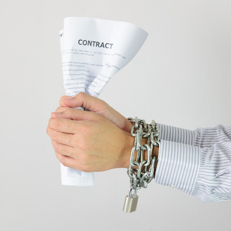 Businessman hands with tied with chains and hold contract