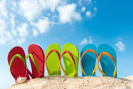 Row of colorful flip flops on beach against sunny sky