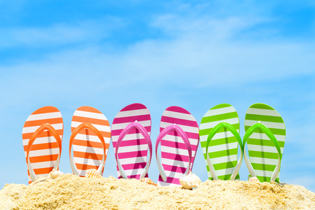 Row of multicolor flip flops on beach against blue sky