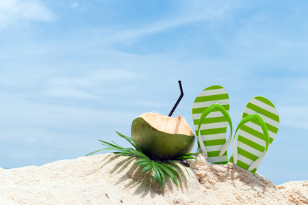 Photo pour Pair of green striped sandal and coconut drink on the beach - image libre de droit