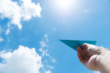 Hand launching paper plane toward cloudy blue sky